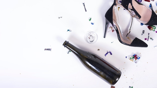Woman black heels lying near bottle after party Free Photo