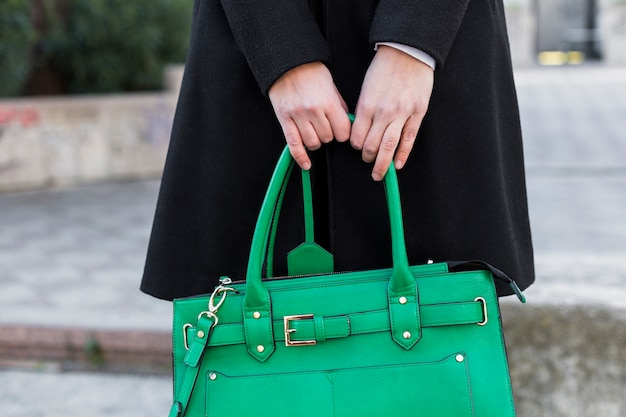 Woman in black holding bag in hands Free Photo
