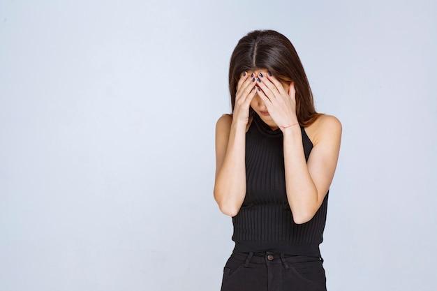 Woman in black shirt has headache or crying. Free Photo