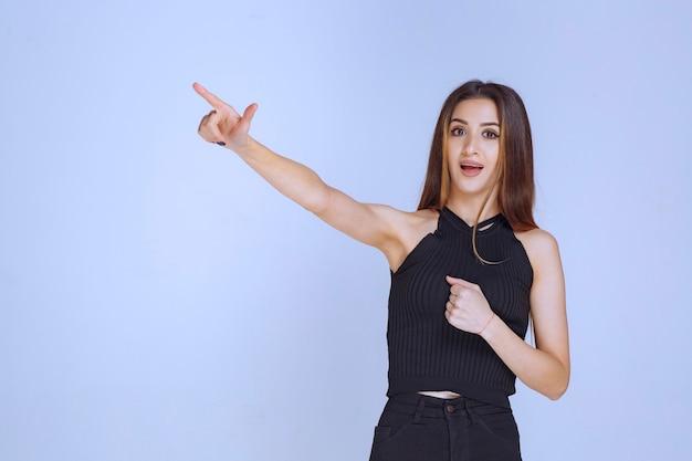 Donna in camicia nera che mostra il segno della mano del perdente. Foto Gratuite