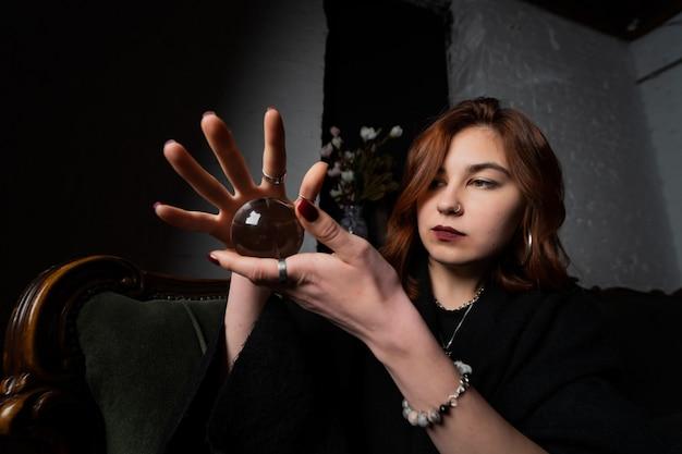 Donna in vestito nero che tiene la sfera di cristallo nelle sue mani Foto Gratuite