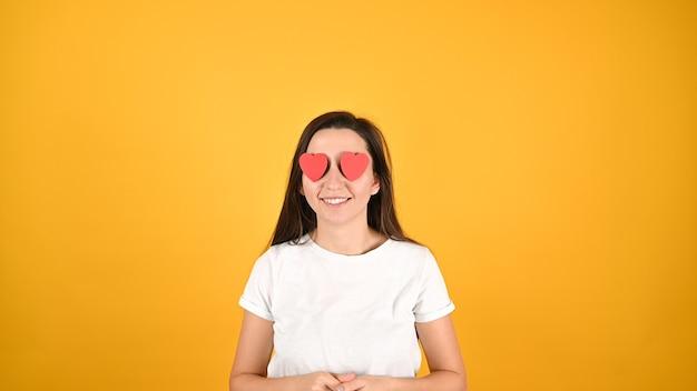 Ослепленная любовью женщина на желтом фоне. Premium Фотографии