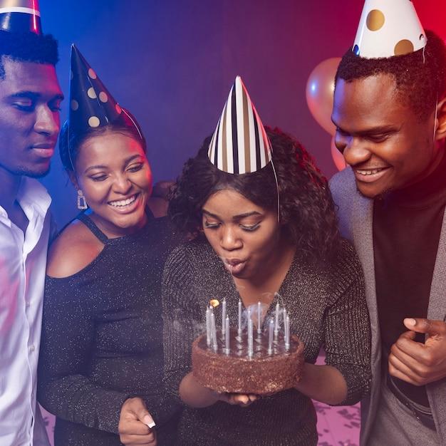 Donna che soffia candele sulla sua torta di buon compleanno Foto Gratuite