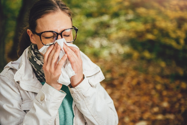 Woman blowing her nose Premium Photo