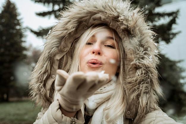 Donna che soffia nella neve dalla sua mano Foto Gratuite