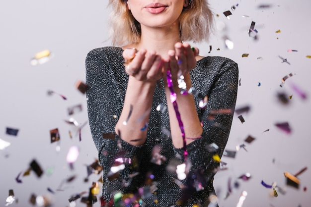 Woman blowing kiss under spangles Free Photo