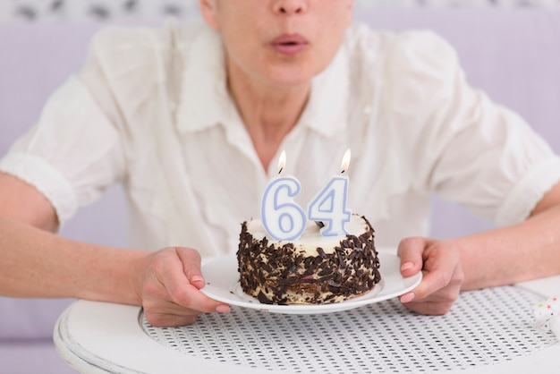 Woman blowing number candles over her birthday cake on table Free Photo