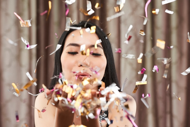 Woman blowing out confetti Free Photo