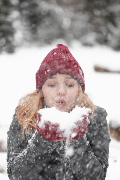 Woman blowing in a pile of snow front view Free Photo