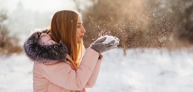Woman blowing snow from hands Free Photo