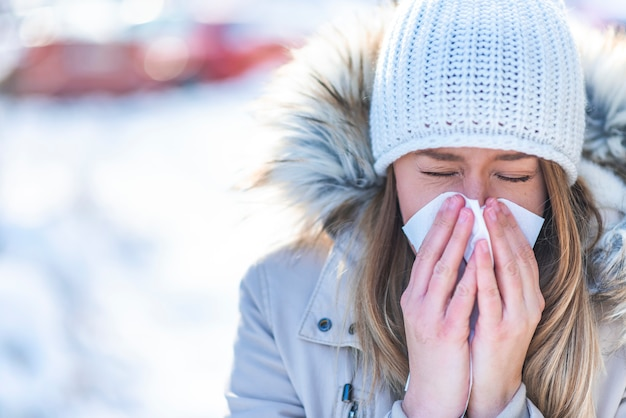 Woman blowing in a tissue in a cold winter with a snowy mountain in the background Premium Photo