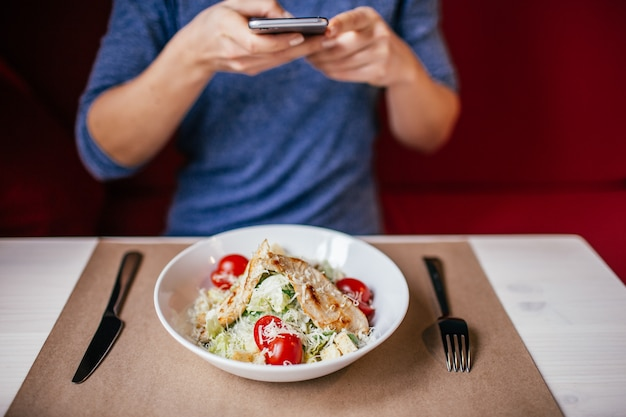 A woman in a blue blouse taking photo of fresh salad caesar on the table with her smartphone Premium Photo