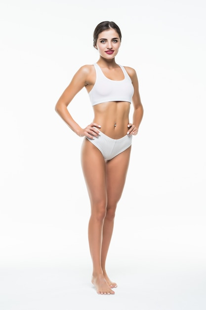 女性の体の美しさ、白い壁に分離された白い下着を歩くスリムなモデル 無料写真