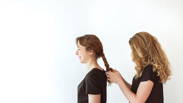 Woman braiding sister's hair isolated over white background Free Photo