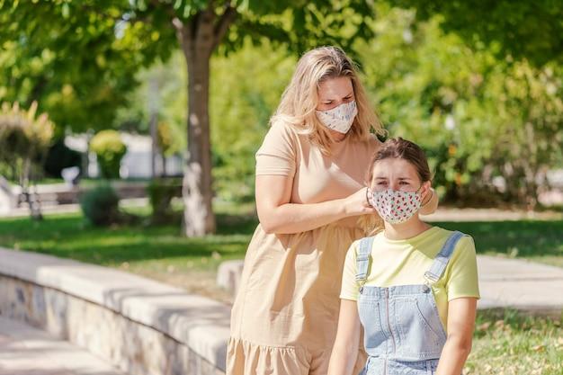 여자는 전염병 동안 공원에서 친구의 머리를 땋습니다. 프리미엄 사진