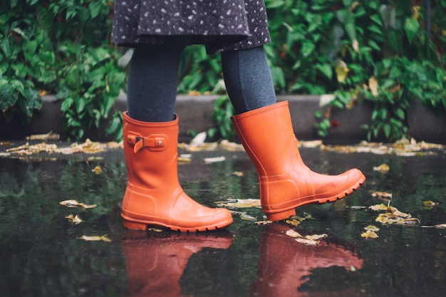 A woman in bright pink rubber boots (gumboots) under the rain. autumn concept Premium Photo