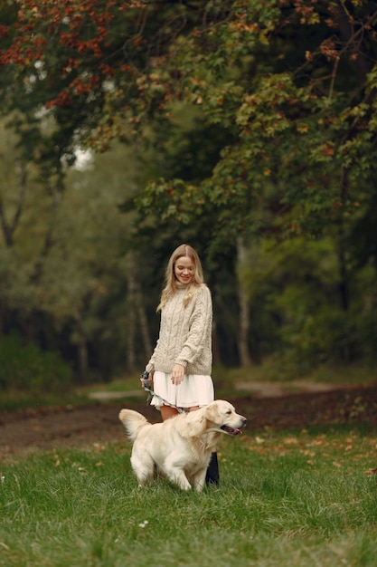 Woman in a brown sweater. lady with a labrador. friends are having fun outside. Free Photo