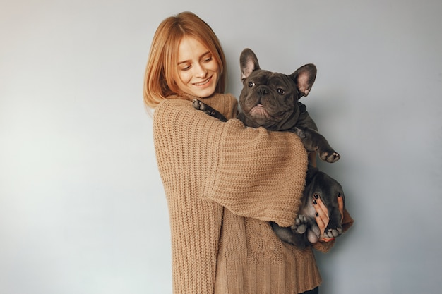 Woman in a brown sweater with black bulldog Free Photo