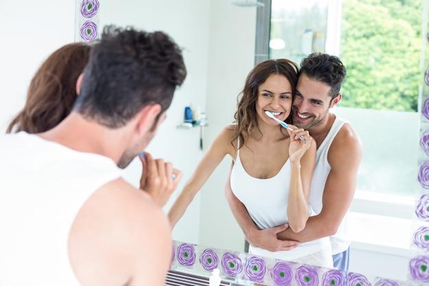 Woman brushing teeth while husband embracing her in bathroom Premium Photo