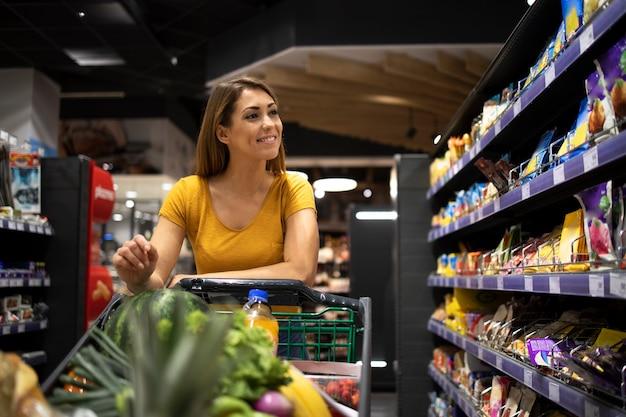 スーパーマーケットで食べ物を買う女性 無料写真