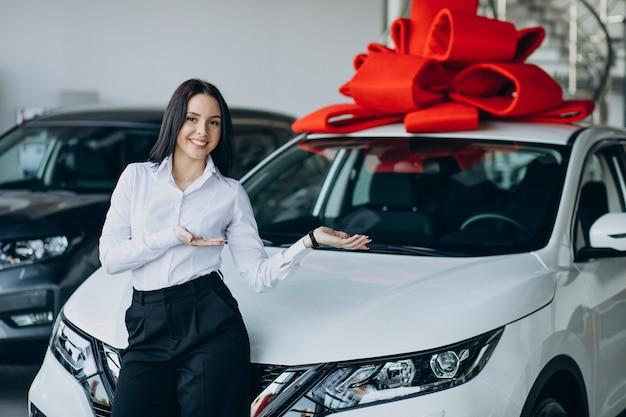 大きな赤い弓を持つ車のそばの女性 無料写真