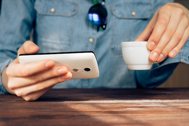 Woman in a cafe holding a cell phone and drinking coffee Premium Photo