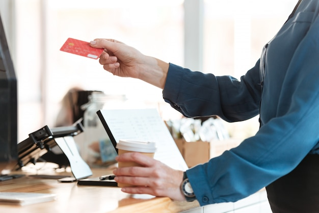 Woman in cafe holding credit card and coffee. Free Photo