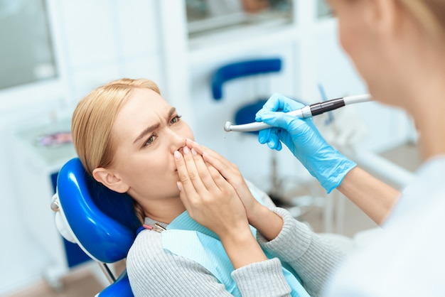 The woman came to see the dentist. the woman is afraid Premium Photo