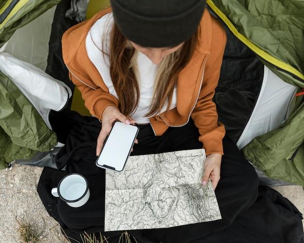 Женщина кемпинг и смотрит на карту Бесплатные Фотографии