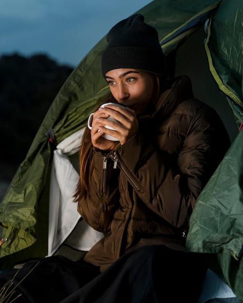 Donna in campeggio e bere una tazza di tè Foto Gratuite