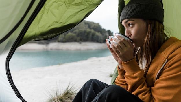 Donna in campeggio e bere il tè lateralmente Foto Gratuite