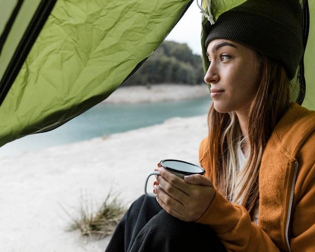 Donna in campeggio e con una tazza di tè Foto Gratuite