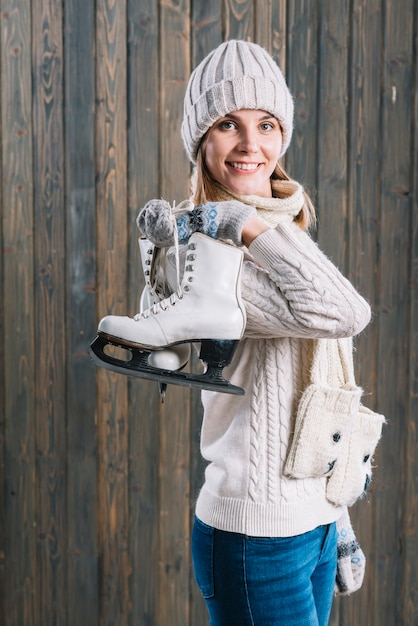 Woman in cap with skates behind back Free Photo