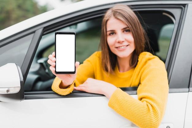 Woman in car showing phone screen Free Photo