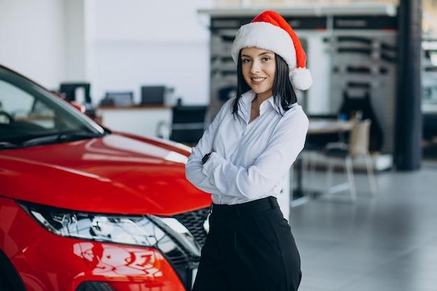 Donna in uno showroom di auto a natale Foto Gratuite