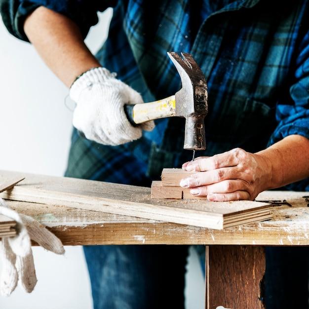 Woman carpenter using hammer pushing nail on a wood Free Photo