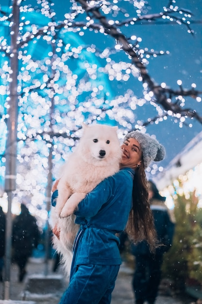 A woman carries her dog in her arms. Free Photo