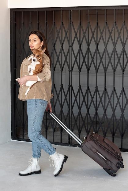 Женщина несет багаж и держит ее собаку Бесплатные Фотографии