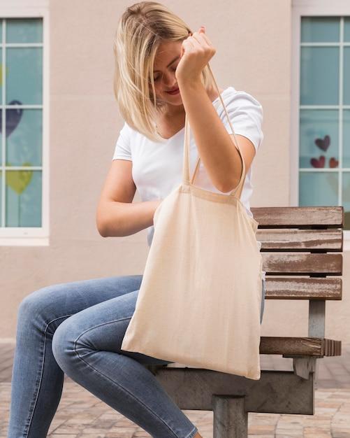 Женщина несет сумку для покупок и ищет в ней Бесплатные Фотографии