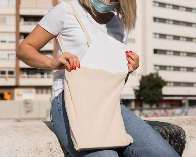 ショッピングバッグを持ってマスクを身に着けている女性 無料写真