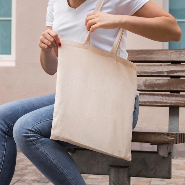 La donna che porta una borsa in tessuto all'esterno Foto Gratuite