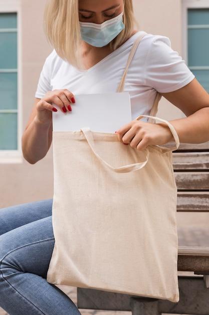 Donna che porta una borsa in tessuto che indossa maschera medica Foto Gratuite