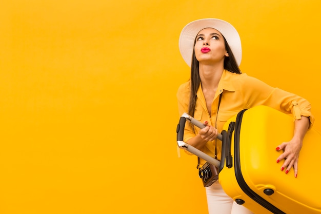 Woman carrying heavy trip luggage with copy space Free Photo