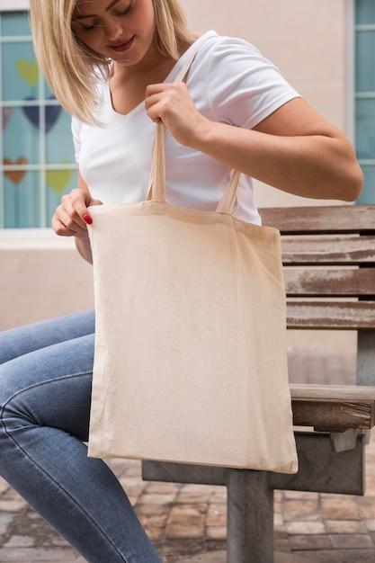 Donna che porta una borsa della spesa e cerca in essa Foto Gratuite