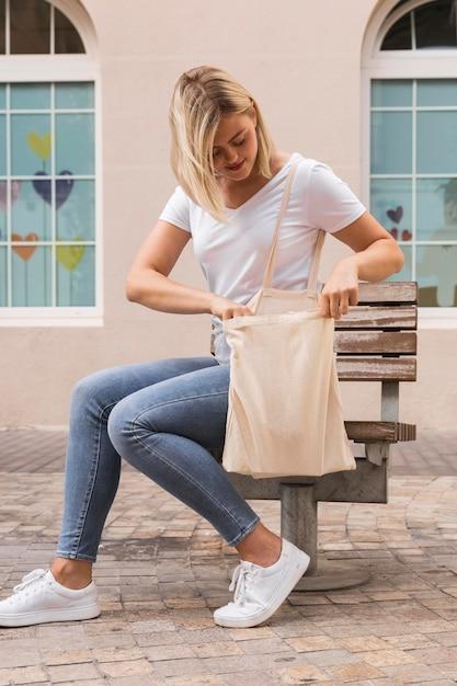 Donna che porta una borsa della spesa all'aperto Foto Gratuite