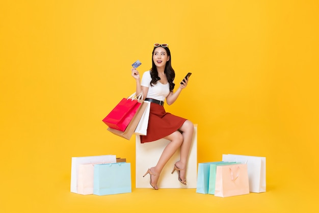 Woman carrying shopping bags with credit card and mobile phone in hands Premium Photo