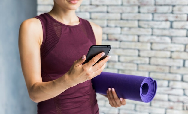 Woman carrying a yoga mat while looking at her phone Free Photo