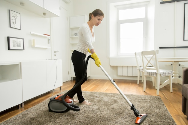 Woman in casual wear vacuum cleaning the carpet Free Photo