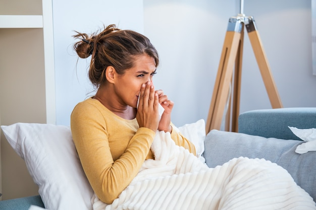 Woman caught cold and flu sneezing into tissue. Premium Photo