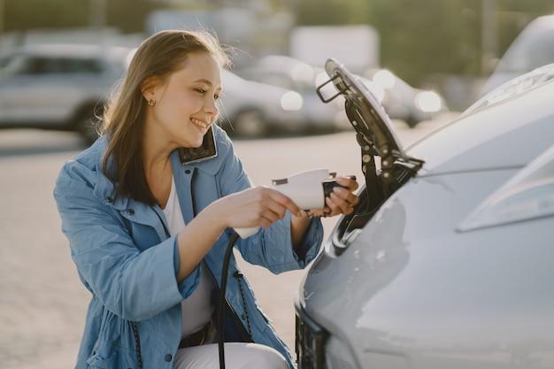 電気ガソリンスタンドで電気自動車を充電する女性 無料写真